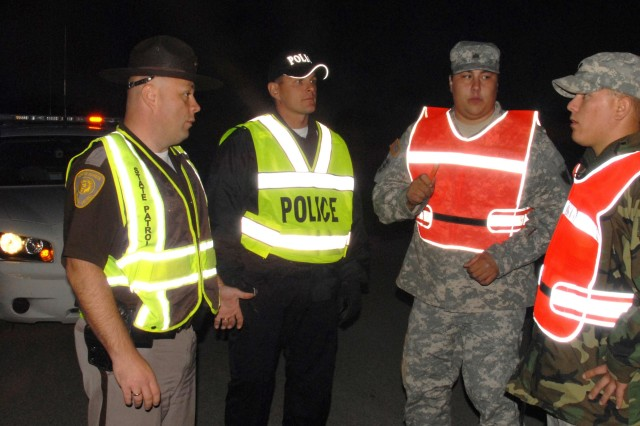 Spc. Shane A. Korynta and Sgt. Danny J. Lemieux Jr. help police man an entry control post on the outskirts of Northwood.