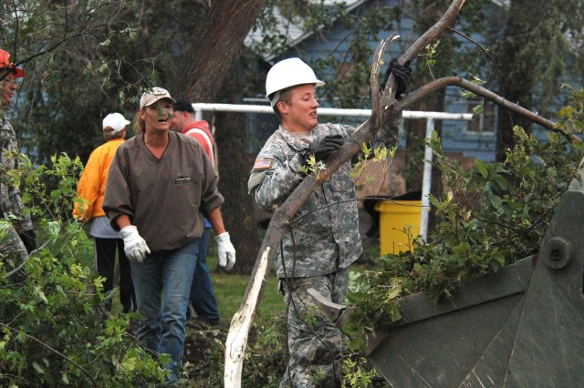 Spc. Joel D. Erickson and other Soldiers pitch in the clear debris.