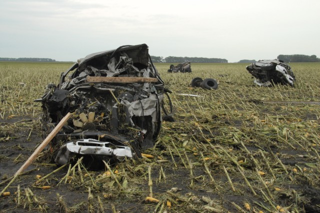 The twister strips ears of corn from stalks and plants cars from a dealership.