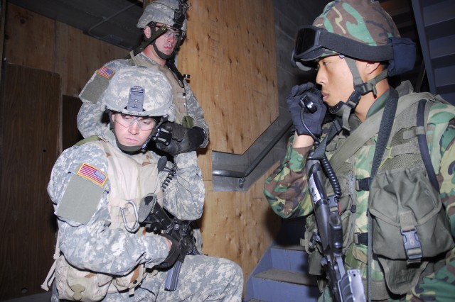 U.S. 2nd Lt. Todd Kluttz (left), 3rd Platoon, C Company, 1st Battalion, 5th Infantry Regiment, 1st Stryker Brigade Combat Team, 25th Infantry Division, tries to contact his unit while working with Singaporean 1st Lt. Tang Siming Clifton, (right) a platoon leader in 4th Battalion Singapore Infantry Regiment, 2nd Brigade, 6th Division. The two soldiers are training together as part of Exercise Lightning Strike at Fort Wainwright, Alaska. (U.S. Army photo by Staff Sgt. Matthew T MacRoberts) (Released)