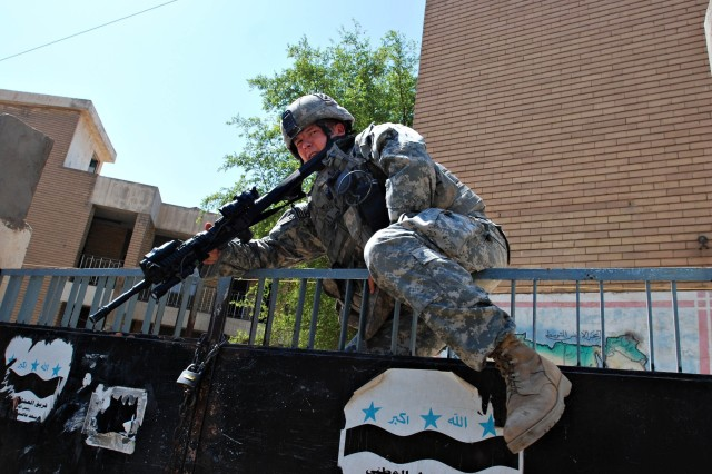 Sgt. 1st Class Joshua Harrison, a platoon sergeant, climbs over a gate to get to the next building.