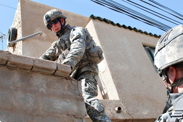 Pfc. Art Fink scales a wall during the search.