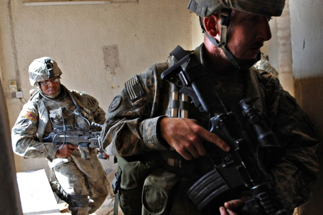 Spc. Christopher Shelton and Staff Sgt. Eric Bull clear a room in an apartment building.
