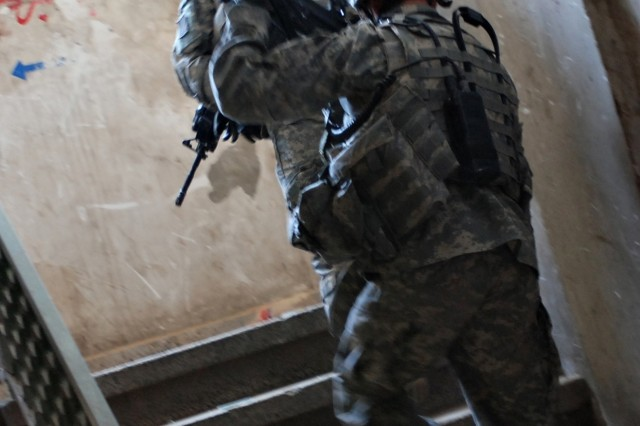 Staff Sgt. Joseph Faulkner and Sgt. 1st Class Larry Doerfler move up a stairwell.