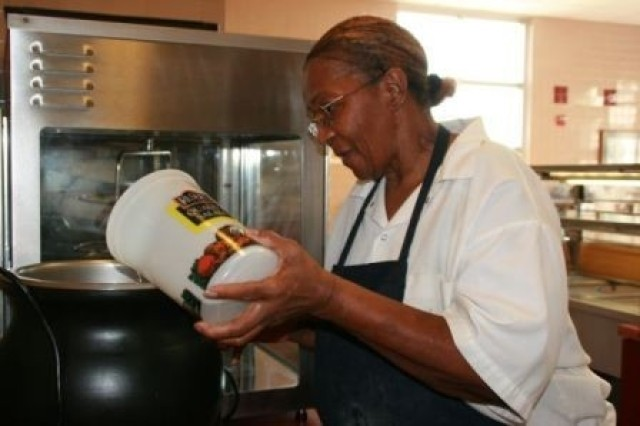 "Faye Coleman, Rocco Dining Facility food server, heats up water to keep the chili hot for the lunch crowd at the dining facility. Ms. Coleman says she loves her job because she has ""a sweet boss who keeps me laughing."""