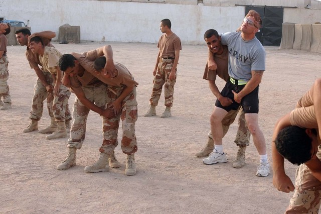 A Soldier from the 10th Mountain Division gives hand-to-hand combat training to Iraqi army recruits.