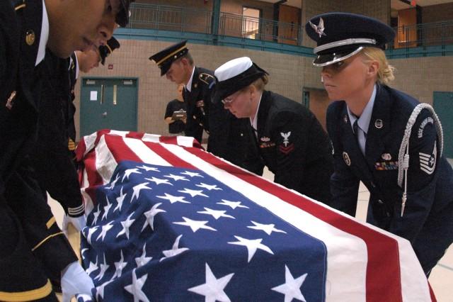 Personnel lower a training casket.