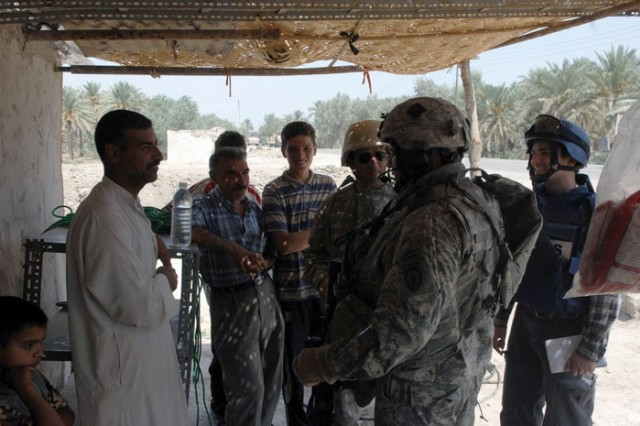 Lt. Col. Robert Balcavage, commander, 1st Battalion, 501st Parachute Infantry Regiment, talks with members of the Concerned Citizens Program during Operation Gecko.