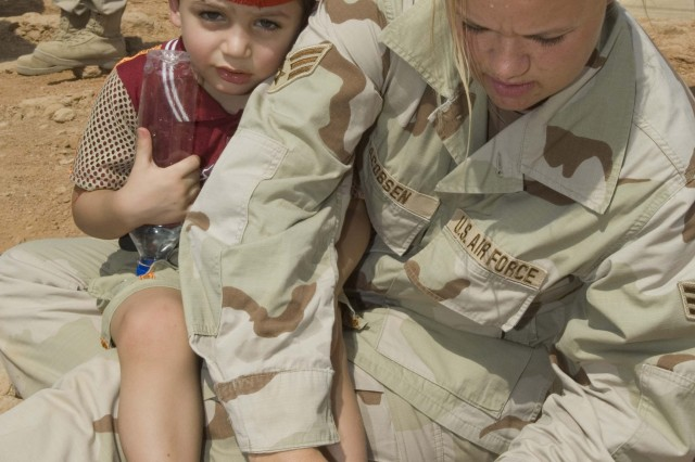 Senior Airman Ashley-Louise Jacobsen, from the 407th Expeditionary Logistics Readiness Squadron, helps an Iraqi boy get a rock out of his sandal.