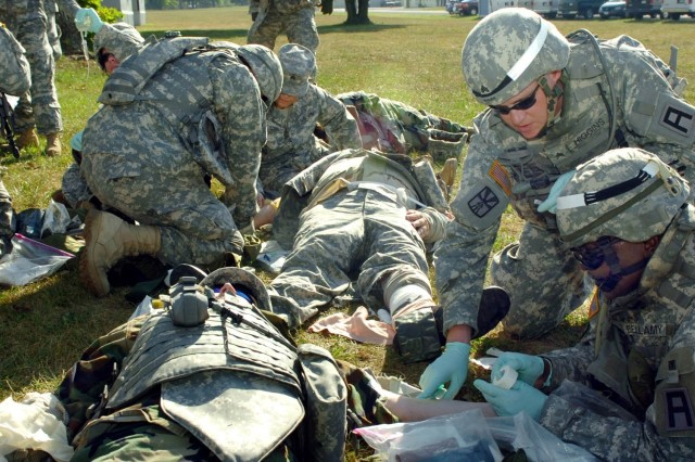 Sgt. Clint Higgins, a combat lifesaver instructor with the 205th Infantry Brigade, helps students taking the combat lifesaver course practice lifesaving skills at Camp Atterbury, Ind. During the final exercise, students practice many of their new skills, including inserting IVs, applying tourniquets and pressure dressings, treating mental trauma, and moving wounded Soldiers to a safe area. U.S.