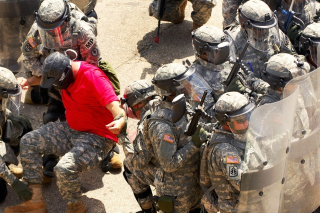 Soldiers face down a crowd of instructors role-playing as rioters