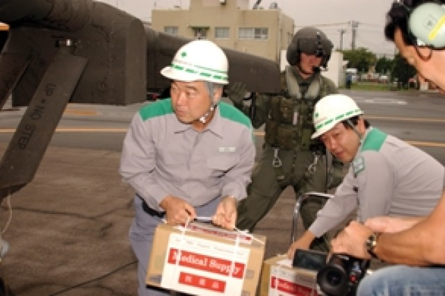 CAMP ZAMA - 78th Aviation Battalion of U.S. Army Japan air crew member Staff Sgt. Robert Dahlen observes Japanese disaster relief workers load medical supplies onto a UH-60 Black Hawk Helicopter during Japan's 2007 National Disaster Prevention Day on September 1 at the Tokyo Metropolitan Heliport. (U.S. Army photo by Christopher Bush)