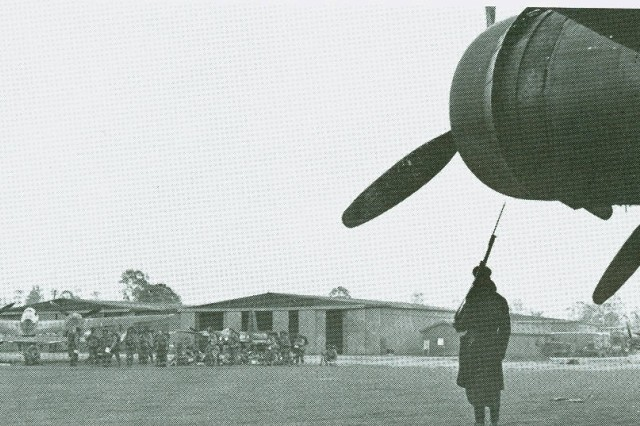 An Australian Airfield,18 September 1942, a Australian sentry is on guard near a Flying Fortress (B-17) in the right foreground as soldiers await planes to go to New Guinea.