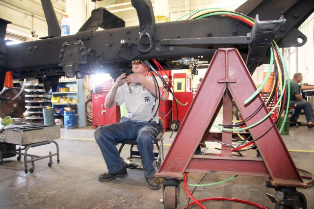 A member of the Red River Army Depot workforce completes electronic work for the HEMTT. RRAD HEMTT maintenance area is the recent recipient of the 2007 Silver Shingo Medallion.