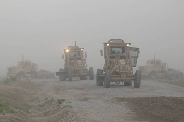 Task Force Pacemaker Soldiers perform road construction during a sandstorm.