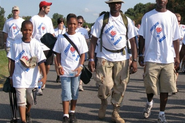 Army Staff Sgt. Curtis Taylor, right, and Army Sgt. Michael Halmon, to his left, both Iraqi war veterans from the 55th Sustainment Brigade on Fort Belvoir, Va., said the Freedom Walk shows that the country remembers those people killed on Sept. 11, 2001, and since in the war on terror. Halmon's children, Rachael and Lafayette, walk alongside him.  Defesne Department Photo.