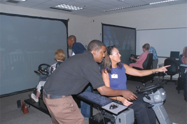 Jill McCoy, wife of Maj. Gen. William McCoy Jr., Fort Leonard Wood commander, receives feedback from instructor Andre Murphy after completing a test drive hauling cargo with the simulator. (photo by Lindy Dinklage)