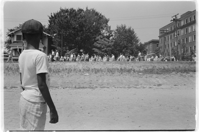 """Photograph shows a young African American boy watching a group of people, some carrying American flags, march past to protest the admission of the """"Little Rock Nine"""" to Central High School.Library of Congress Prints and Photographs Division Washington, D.C. 20540 USA"""