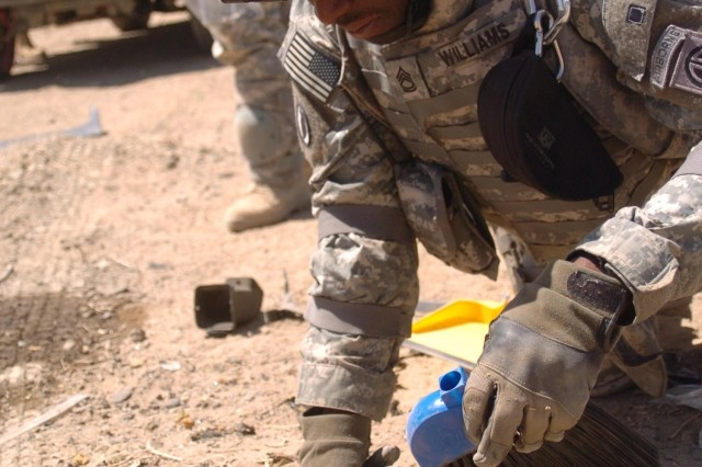 A Military Post-blast Investigative Course student collects a soil sample during a post-blast scene exploitation as part of a course field exercise August 30, at Bagram Airfield, Afghanistan.