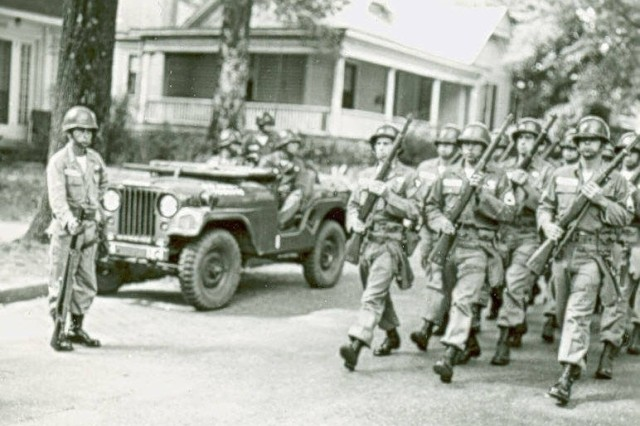 "101st Airborne Soldiers march in formation down a road in Little Rock, Arkansas.  President Eisenhower's Executive Order had been activated as the ""Screaming Eagles"" brought order to the chaiotic and increasingly violent mob protesting integration.  Library of Congress Prints and Photographs Division Washington, D.C. 20540 USA"
