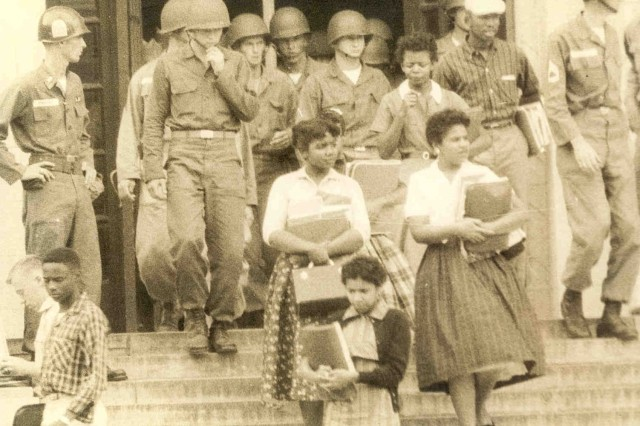 Several of the Little Rock Nine leave Central High School under troop escort, 1957.