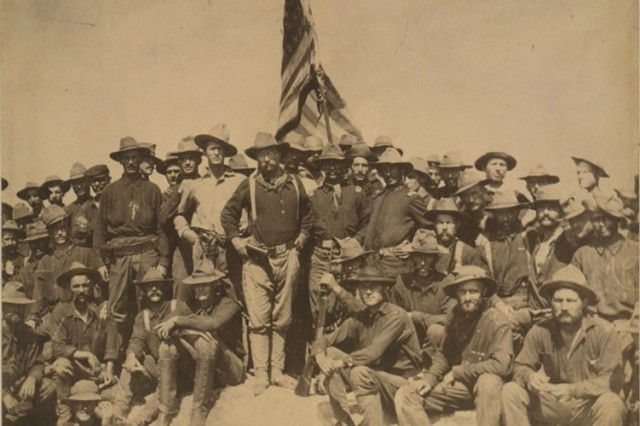 "Roosevelt's ""Rough Riders"" pose for a group photo while proudly displaying the American flag."