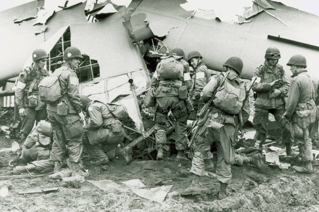 """101st Airborne Division troops that landed behind German lines in Holland examine what is left of one of the gliders that """"cracked up.""""(WW2 Signal Corps photograph collection)."""