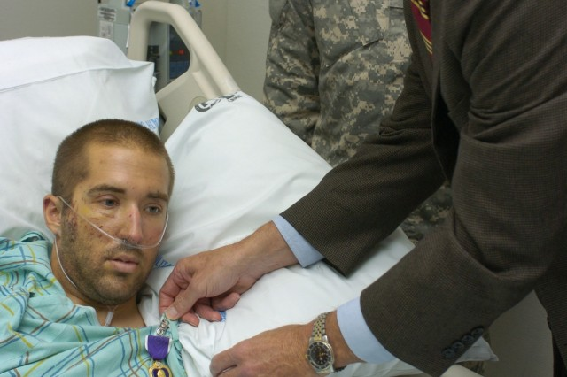 Secretary of the Army Pete Geren presents the Purple Heart to Spc. Jonathan Pruschner at Landstuhl Regional Medical Center, Germany, Sept. 14.
