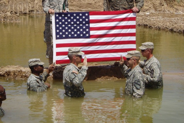 "Soldiers from Company A, 1st Battalion, 12th Cavalry Regiment, 1st Cavalry Division, reenlist near Baqubah, Iraq, at ""Apache Lake,"" site of the Soldiers' favorite swimming hole. Following the ceremony, the Soldiers had some mud wrestling fun."