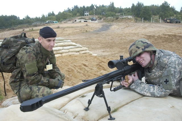 Sgt. Chad Droege, Illinois Army National Guard, learns how to fire a Polish sniper rifle from Polish army Cpl. Lukasz Bocwinski during Immediate Response 07 at the Wedrzyn Training Area in Poland.