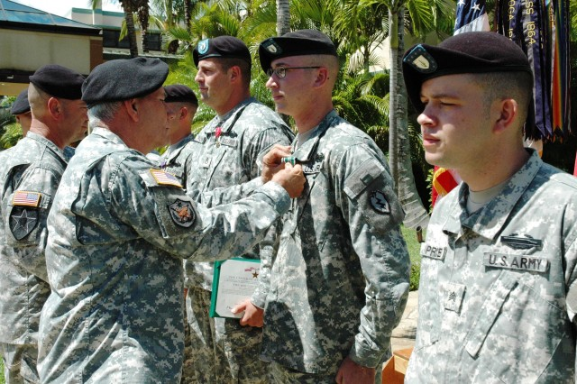 "Maj. Gen. William Brandenburg, 8th Theater Sustainment Command, pins an Army Commendation ""V"" device on Sgt. Ernst Bennett, 2nd Battalion, 35th Infantry Regiment, at the Schofield Barracks Tropic Lightning Memorial, Friday."