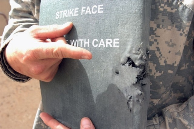 Sgt. Jason Stegall shows the armor plate that was struck during a small-arms firefight, for which he received the first of his two Purple Heart medals