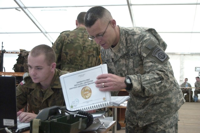 Sgt. Maj. Robert Priest reviews plans for an upcoming training mission during the exercise Immediate Response 07 held in Poland.