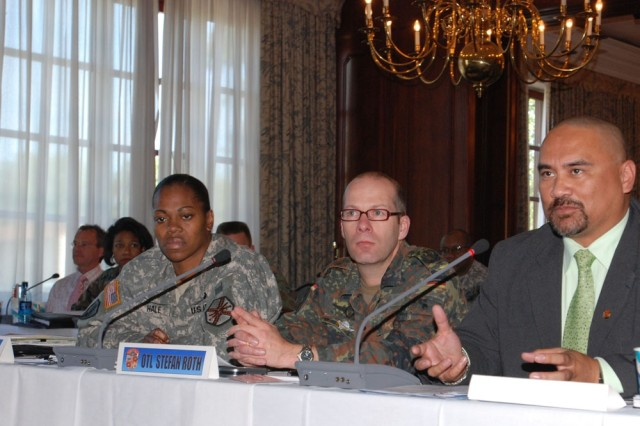Henry Kaaihue, USAG Kaiserslautern force protection and consequence management section chief, discusses his community's emergency response procedures during Exercise Guardian Shield 2007 which took place in the Patrick Henry Village Pavilion Sept. 11-13. Other members of the Kaiserslautern community's delegation included Lt. Col. Mechelle Hale, U.S. Army Garrison Kaiserslautern commander, and Oberstleutnant d.R. (reserve Lt. Col.) Stefan Roth, representing the Kaiserslautern County department of Military-Civilian Cooperation.