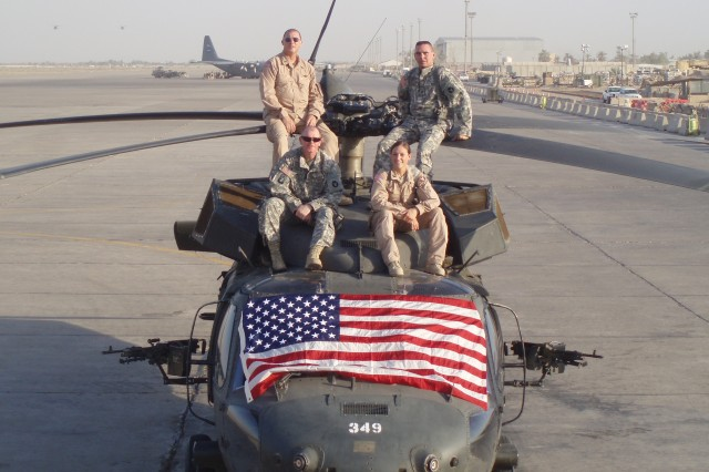A flight crew from 2nd Battalion, 147th Aviation Regiment sits on top of their patriotic UH-60 Black Hawk helicopter at Baghdad International Airport, Iraq. The 2-147th is a Minnesota National Guard battalion attached to the 12th CAB as part of Task Force XII. Pictured are Chief Warrant Officer Bill Rawling, Capt. Andrea Ourada, Sgt. Jeffrey Miles and Sgt. Roger Gibeault. (U.S. Army photo by Spc. Jaren Lukach, 2-147th)
