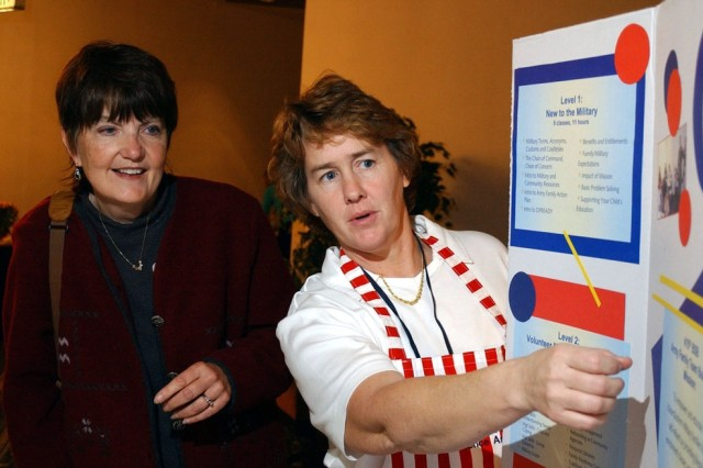 Mary Lou Smith (left), listens to Baumholder volunteer Erin Kantor explain Army Family Team Building at a past American Women's Activities, Germany, conference.