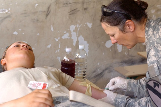 Staff Sgt. Lori Naifeh, 115th Brigade Support Battalion, administers an IV to a dehydrated Soldier during medical operations in Hor Al Bosh, Iraq, July 15. Beginning Oct. 1, Soldiers entering Basic Combat Training will receive Combat Lifesaving Training and be CLS certified before graduation.