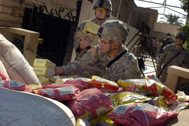 Staff Sgt. Moorehead, from the 422nd Civil Affairs Battalion, and Spc. Justin Reed of Battery A, 3rd Battalion, 82nd Field Artillery Regiment, 2nd Brigade Combat Team, 1st Cavalry Division, unload a trailer full of food being dropped off at a home for children affected by mental illness during a humanitarian aid drop in central Baghdad's Qadisiyah neighborhood Sept. 18.