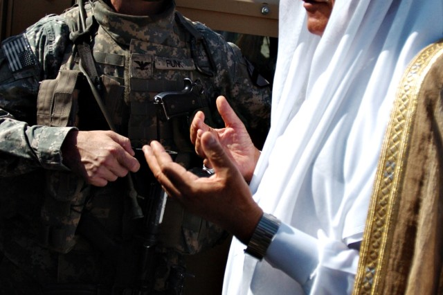 """Roundup, Mont., native Col. Paul E. Funk II, commander of the 1st """"Ironhorse"""" Brigade Combat Team, 1st Cavalry Division, speaks with a local sheik in the village of Jubeb, near Abu Ghraib, Iraq Sept. 19. The meeting was part of a trend toward cooperation in Abu Ghraib, where an """"awakening"""" of Sunni sheiks sparked the growth of a homegrown security force. These citizens grew tired of the violence of Sunni extremists in the area and took up arms in support of the Coalition."""