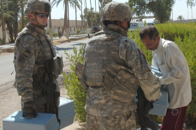Sgt. Thomas Fogarty (left), a native of Alameda, Calif. and Sgt. Paul Gomez, who hails from San Antonio, both Soldiers serving on a 1st Brigade Combat Team, 1st Cavalry Division personal security detachment, deliver soil testing kits to a faculty member from the University of Baghdad's College of Agriculture in Abu Ghraib, Iraq Sept. 22 during a visit to the facility's campus.