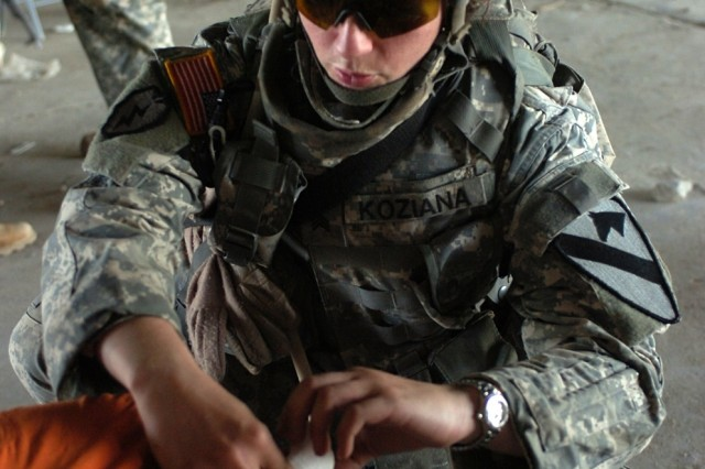Sgt. Amy Koziana, a Killeen, Texas, native and healthcare specialist with Company C, 15th Brigade Support Battalion, bandages an Iraqi boy's toe during a cooperative medical engagement spearheaded by Company D, 4th Squadron, 9th Cavalry Regiment Sept. 20.