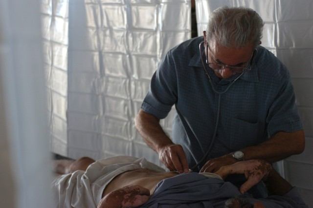 An Iraqi doctor listens to a man's heartbeat inside the mobile aid station built by Soldiers from Company D, 4th Squadron, 9th Cavalry Regiment in central Baghdad's Karkh District during a cooperative medical engagement Sept. 20.