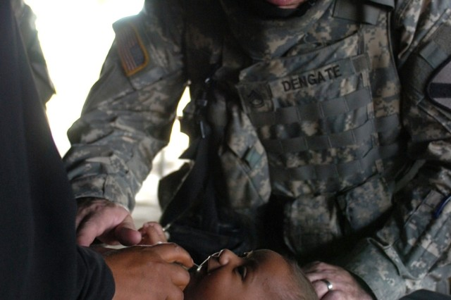 Sgt. 1st Class Mark Dengate, Headquarters and Headquarters Company, 2nd Brigade Combat Team, 1st Cavalry Division, examines an Iraqi baby brought to a cooperative medical engagement in Baghdad's Karkh District Sept. 20.