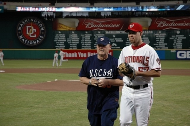 Coast Guard Commandant Adm. Thad W. Allen flanked by Washington Nationals pitcher Jason Bergmann, prepares to throw out a ceremonial first pitch to kick off the 2007 Combined Federal Campaign for the national capital area before the start of the Nationals-Philadelphia Phillies Major League Baseball game at RFK Memorial Stadium in Washington, D.C., Sept. 21.