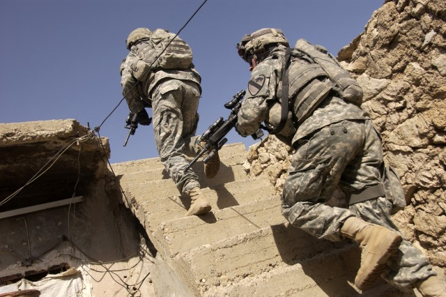 Soldiers climb to a rooftop to take up overwatch positions, protecting their fellow Soldiers who are visiting the neighborhoods.