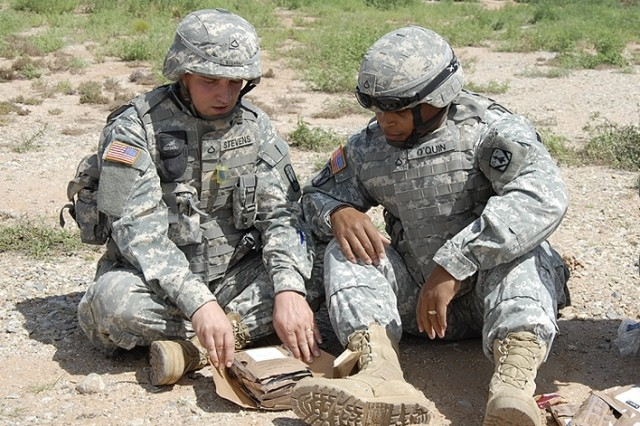 Two Soldiers look at the components of the First Strike Ration during a recent evaluation in Fort Bliss, Texas.