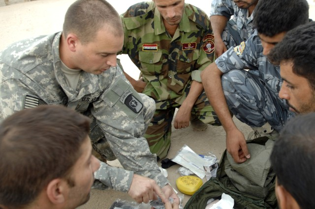 Spc. Keith Rudd, from the 250th Forward Surgical Team, 82nd Airborne Division, reviews the contents of a medical kit with Iraqi police officers from the An Nasiriyah Tactical Support Unit during a combat casualty treatment course at Camp Mitica.