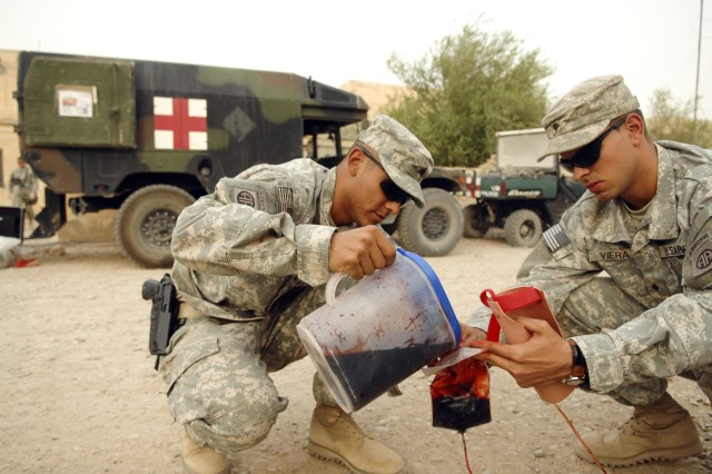 Sgt. Joel Ruiz and Spc. Osniel Viera, from the 82nd Sustainment Brigade, pour fake blood into an intravenous bag during a combat casualty treatment course for Iraqi police recruits at Camp Mitica.