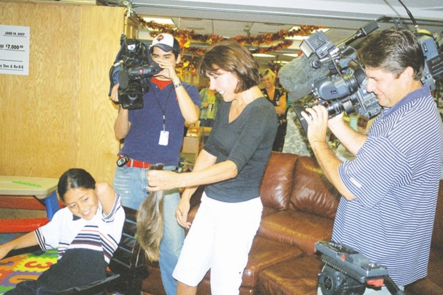 Vera Canedy cuts off 10 inches of Gabriel Macias' hair Sept. 11 at the Warrior and Family Support Center with an audience of local TV reporters. Macias donated his hair to Locks of Love, a nonprofit organization that provides hairpieces to children suffering from long-term medical hair loss.