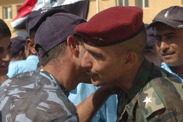 An Iraqi Police graduate hugs Lt. Omar Thamer, an Iraqi Police officer instructor, after the graduation ceremony at Camp India Sept. 25.